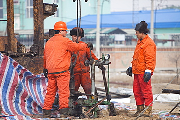 Oil workers drilling a new oil well in the Daqing oil field in Northern China, Asia