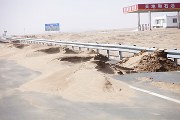 Sand dunes spreading across a highway in Inner Mongolia, China, Asia