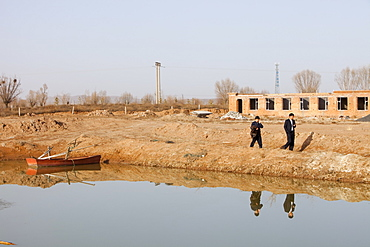 A small reservoir dug out in an attempt to find water, the new building in the background has been built on the original lake bed level, Hong Hai Zai, near Dongsheng, Inner Mongolia, China, Asia