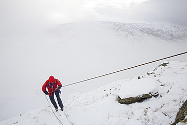 A mountain rescue team member abseiling in the snow above Kirkstone near Ambleside in the Lake District, Cumbria, England, United Kingdom, Europe