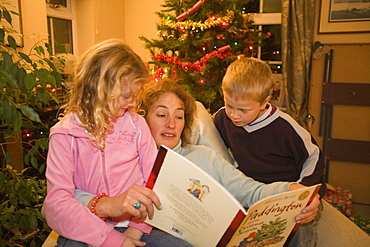 An auntie reads a Christmas story to her neice and nephew at Christmas time, United Kingdom, Europe