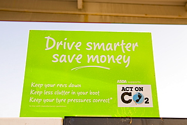 A sign on a petrol pump at a supermarket petrol station advising motorists to drive more efficiently