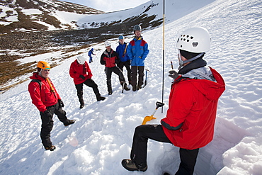A member of the Scottish Avalanche Information Service demonstrates how to assess avalanche risk on Cairngorm in the Cairngorm National Park in Scotland, United Kingdom, Europe