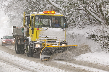 A snow plough driving in heavy snow in Ambleside, Cumbria, England, United Kingdom, Europe