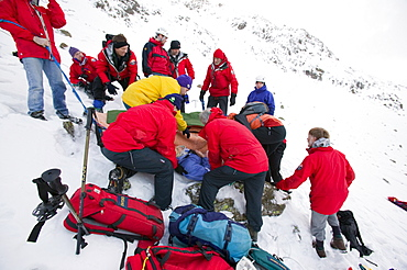 Mountain rescue team members rescue a seriously injured women from Red Screes who had fallen 300 feet in the snow, Lake District, Cumbria, England, United Kingdom, Europe