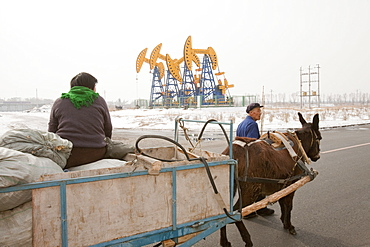 A peasant farmer and his donkey cart in front of nodding donkey oil pumps pumping oil up from the Daqing oil field in Northern China, Asia
