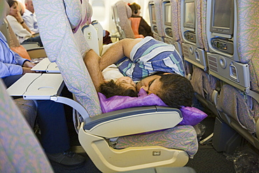 A father and daughter asleep together on an Emirates flight