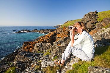 A woman birdwatching on the Cornish coast near Pendeen Watch, Cornwall, England, United Kingdom, Europe
