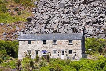 A house overshadowed by boulders from an old quarry at Lamorna Cove in Cornwall, England, United Kingdom, Europe