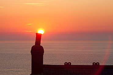 The sun setting over a house chimney at Cape Cornwall, Cornwall, England, United Kingdom, Europe