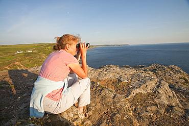 A woman birdwatching on sea cliffs on Cape Cornwall in Cornwall, England, United Kingdom, Europe