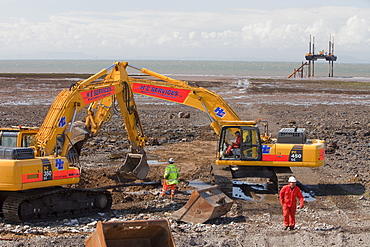 Construction workers working on the foreshore of the Solway Firth near Workington, Cumbria, England, United Kingdom, Europe