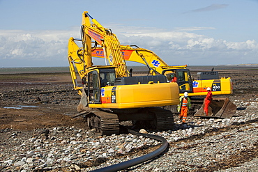 Construction workers installing a power cable on the foreshore of the Solway Firth near Workington, Cumbria, England, United Kingdom, Europe