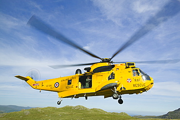 RAF Sea King Helicopter about to land on Crinkle Crags to evacuate an injured walker being treated by a mountain rescue team, Lake District, Cumbria, England, United Kingdom, Europe
