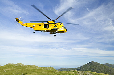 A helicopter comes to evacuate an injured walker on Bow Fell in the Lake District. Cumbria, England, United Kingdom, Europe