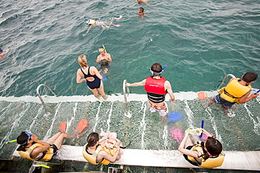 Tourists snorkelling from a dive and snorkel platform anchored to the Great Barrier Reef off Cairns in Queensland, Australia, Pacific