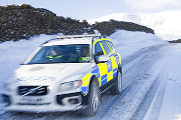 A Police car tries to get over the Kirkstone Pass road above Windermere after it is blocked by spindrift and wind blown snow, Lake District, Cumbria, England, United Kingdom, Europe