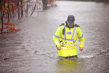 PC Paul Burke wading through floodwaters on Bog Lane near Ambleside, Cumbria, England, United Kingdom, Europe