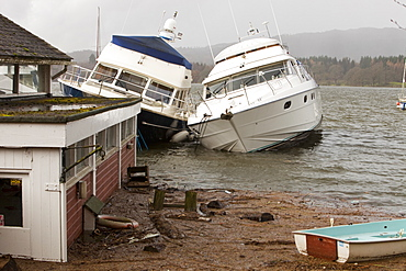 Boats sunk and damaged after Lake windermere rose to its highest ever recorded level in Ambleside, Lake District, Cumbria, England, United Kingdom, Europe