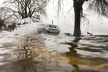 Car driving through floodwater in Ambleside when Lake Windermere broke its banks and spilled over onto the road, Lake District, Cumbria, England, United Kingdom, Europe