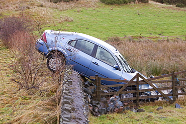 A crashed car after it careered off the road in the floods near Keswick, Lake District, Cumbria, England, United Kingdom, Europe