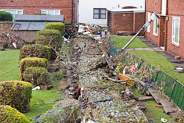 Walls knocked over by the pressure of flood water near Cockermouth's Main street, after the water receded, Cumbria, England, United Kingdom, Europe