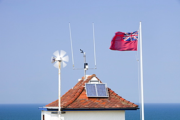 A wind turbine and solar panel on the roof of the Sheringham Coast Watch building, Norfolk England, United Kingdom, Europe