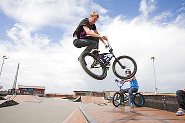 Teenage boys perform aerial stunts on BMX bikes at a BMX park in Rhyl, North Wales, United Kingdom, Europe