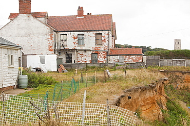 Houses that have already lost gardens to the sea on one of the most rapidly eroding coastlines in the British Isles, Happisburgh, North Norfolk, England, United Kingdom, Europe