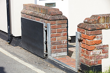 A house in Wells Next the Sea with a flood gate to protect against storm surge coastal flooding, Norfolk, England, United Kingdom, Europe