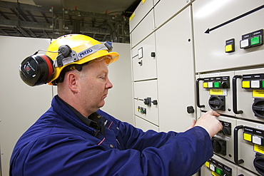An electrician working a control panel in Krafla geothermal power station, Iceland, Polar Regions