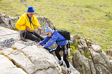 A couple in their 70's rock climbing on a sea cliff at Bosigran on the Cornish coast, England, United Kingdom, Europe