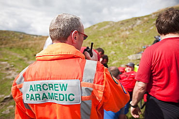 A man with a leg injury is treated by members of the Langdale Ambleside Mountain Rescue Team before being evacuated by air ambulance, above Grasmere, Lake District, Cumbria, England, United Kingdom, Europe