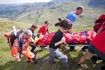 A man with a leg injury is stretchered towards an air ambulance by members of the Langdale Ambleside Mountain Rescue Team, above Grasmere, Lake District, Cumbria, England, United Kingdom, Europe
