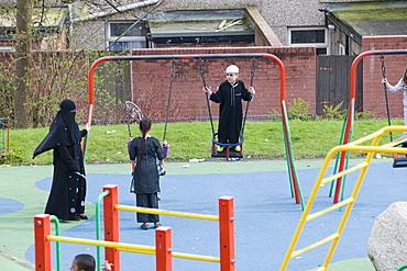 Muslims including a women in a burkha in a playground in a Muslim area of Blackburn, Lancashire, England, United Kingdom, Europe