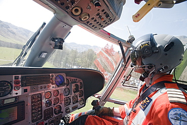 North West Air Ambulance pilot flies mountain rescue team members to a casualty site on the Langdale Pikes, Lake District, Cumbria, England, United Kingdom, Europe