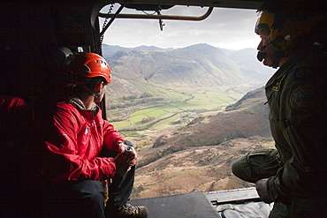 Member of Langdale Ambleside Mountain Rescue team and an RAF winch man in an RAF Sea King helicopter during a rescue in Dungeon Ghyll in the Langdale Pikes Lake District, Cumbria, England, United Kingdom, Europe