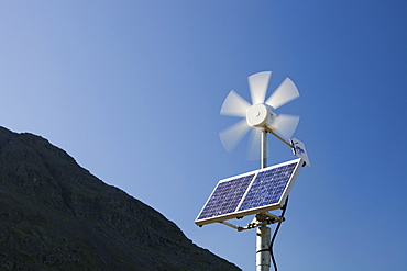 A solar electric panel and wind turbine being used to power a neon road sign on Kirkstone Pass, Lake District, Cumbria, England, United Kingdom, Europe