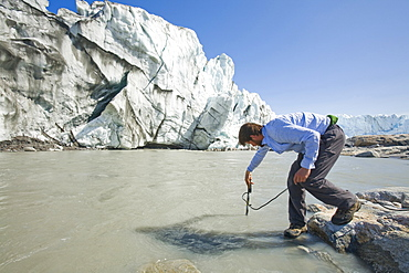 PHD scientist Ian Bartholomew taking measurements as part of a study to measure the speed of the Russell Glacier near Kangerlussuaq, Greenland, Polar Regions