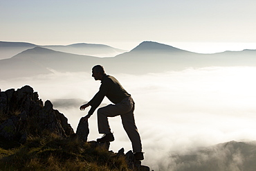 A mountaineer overlooks a temperature inversion with valley mist from Red Screes, looking towards the Kentmere Fells near Ambleside, Lake District National Park, Cumbria, England, United Kingdom, Europe