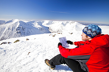A mountaineer checks his map whilst looking towards the Angels Peak and Braeriach across the Lairig Ghru from the summit of Ben Macdui in winter, Cairngorms, Scotland, United Kingdom, Europe