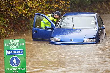 PC Paul Burke examining an abandoned flooded out car near Ambleside, Cumbria, England, United Kingdom, Europe