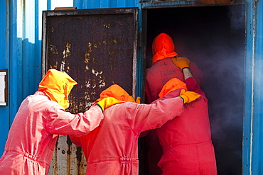 Workers in the offshore industry practise escaping from a smoke chamber as part of an industry training course, Billingham, Teesside, England, United Kingdom, Europe