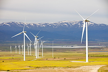 A wind farm near La Calahorra with the world's largest solar power station in the background, Andalucia, Spain, Europe