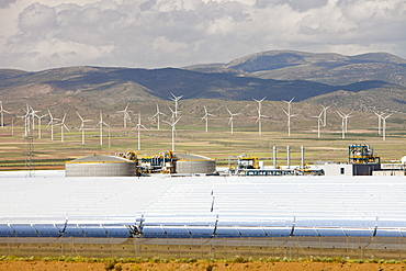 The Andasol solar power station near Guadix with a wind farm in the background, Andalucia, Spain, Europe