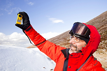 A mountaineer using an anemometer to measure wind speed and wind chill, in the Cairngorm mountains, Scotland, United Kingdom, Europe