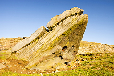 A boulder of millstone grit on Ilkley moor with a perfect circular hole probably formed by a large inclusion weathered out of the bedrock, West Yorkshire, England, United Kingdom, Europe