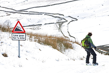 A man snow boarding down from the summit of Kirkstone Pass in the Lake District, Cumbria, England, United Kingdom, Europe