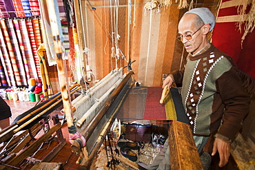 An old man working a loom to weave traditional Moroccan cloth in a souk in Marrakech, Morocco, North Africa, Africa