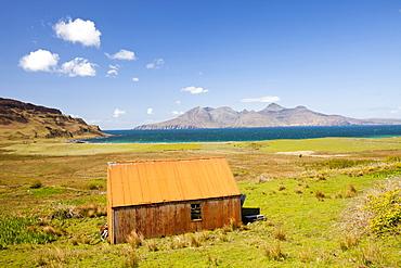 An old corrugated iron barn at Cleadale on the Isle of Eigg, looking towards the Isle of Rhum, Scotland, United Kingdom, Europe
